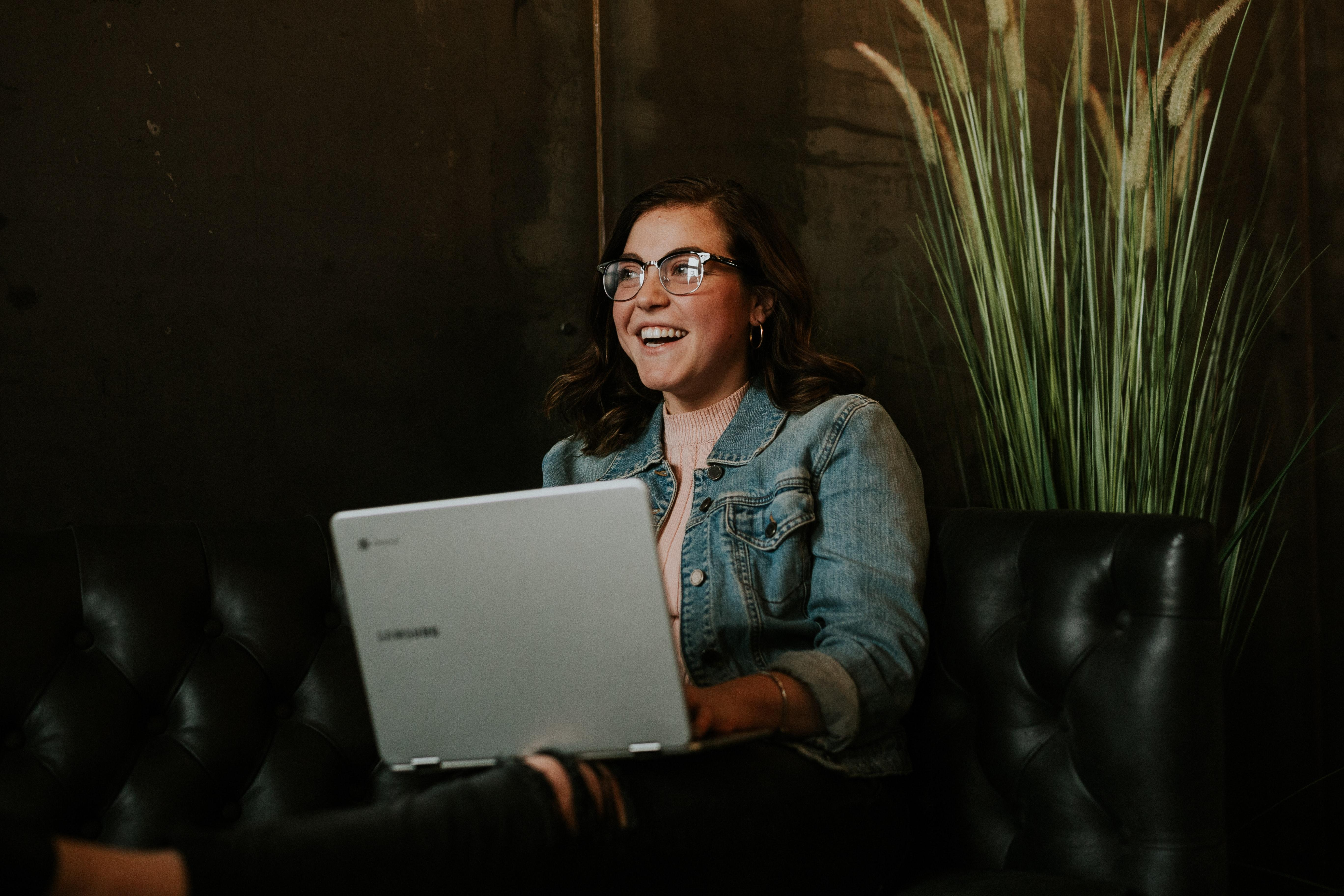Photo of woman smiling behind computer